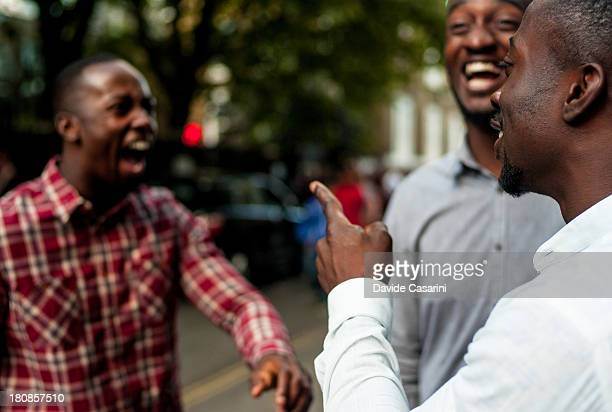 Three boys joking and laughing on the street