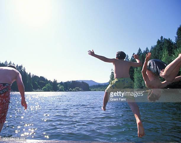 Three boys (11-16) jumping in lake, rear view