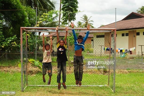 three boys jumping in the air in soccer goal Banda Aceh Sumatra Indonesia