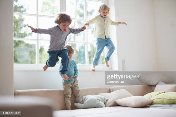 three boys jumping off windowsill onto sofa, mid air - jumping stock pictures, royalty-free photos & images