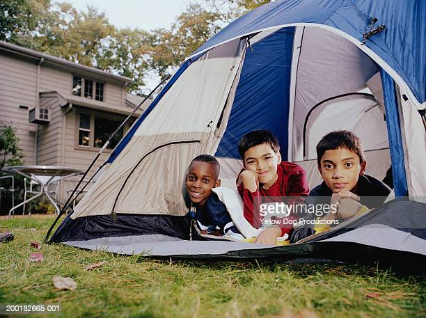 Three boys (10-12) lying in tent, portrait, autumn