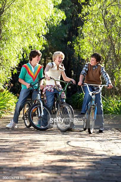 Three boys (9-13) on bikes, smiling