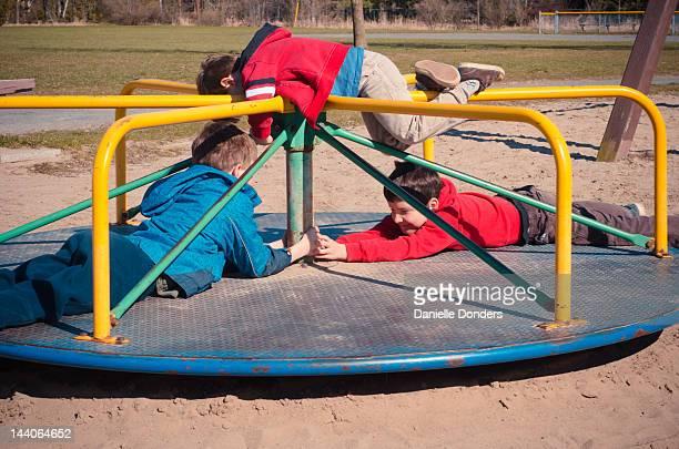 Three boys on playground carousel