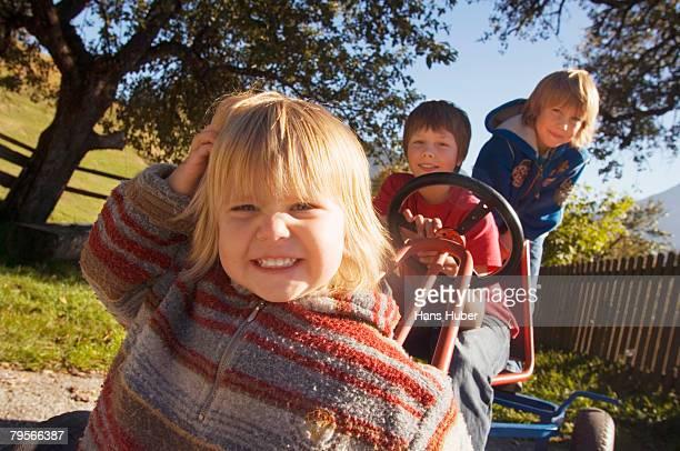 'Three boys on toy car, outdoors'