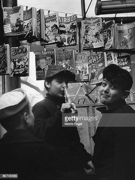 Three boys one with a bottle of soda stand in a shop near a clothesline that holds the latest editions of a number of comic books New York New York...