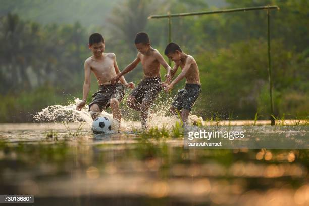 Three boys playing football in a waterlogged field, Thailand