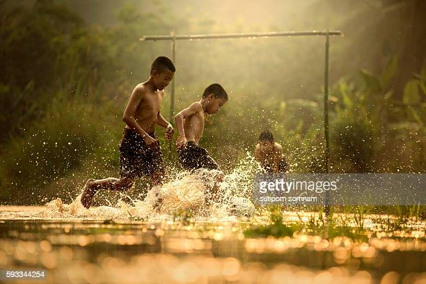 Three boys playing football in the brook