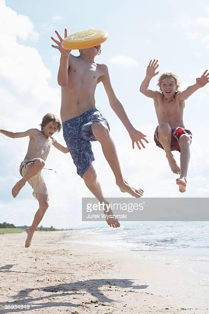three boys playing frisbee on the beach - jungen in badehose 12 jahre stock-fotos und bilder