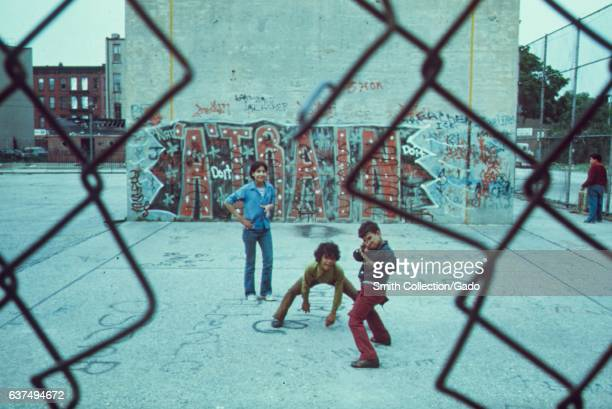 Three boys playing from behind a chain link fence in Brooklyn's Lynch Park graffiti 'A Train' in the background New York City New York June 1974...
