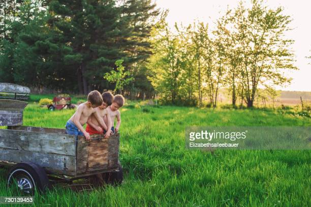 Three boys playing in an old farm wagon