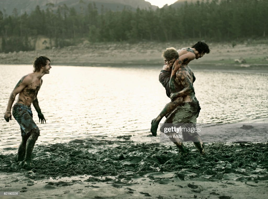 Three boys playing in mud : Stock Photo