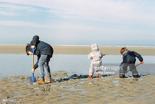 Three boys playing on beach in winter