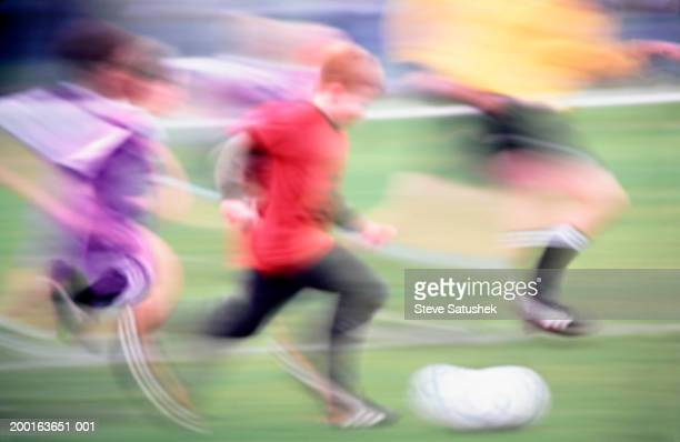 Three boys (8-10) playing soccer, side view, summer (blurred motion)