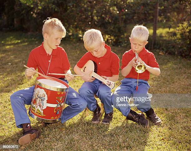 Three Boys Playing Toy Instruments Outdoors