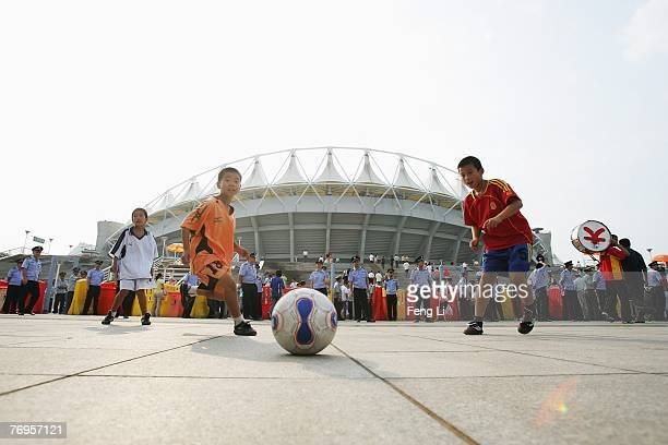 Three boys plays football before the quarter final match of FIFA Women's World Cup China 2007 at Wuhan Sports Center Stadium on September 22 2007 in...