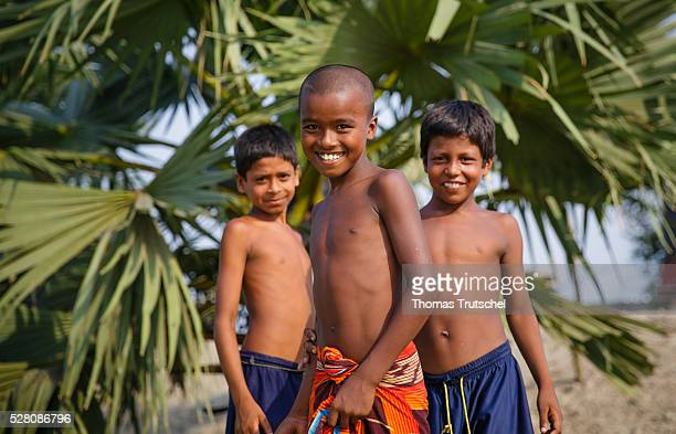 Three boys pose for a photo in front of palms on April 11 2016 in Khulna Bangladesh