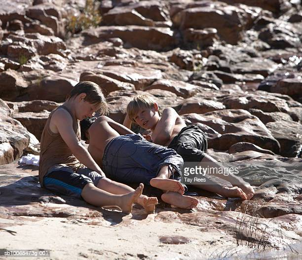 Three boys (10-13) resting on rock