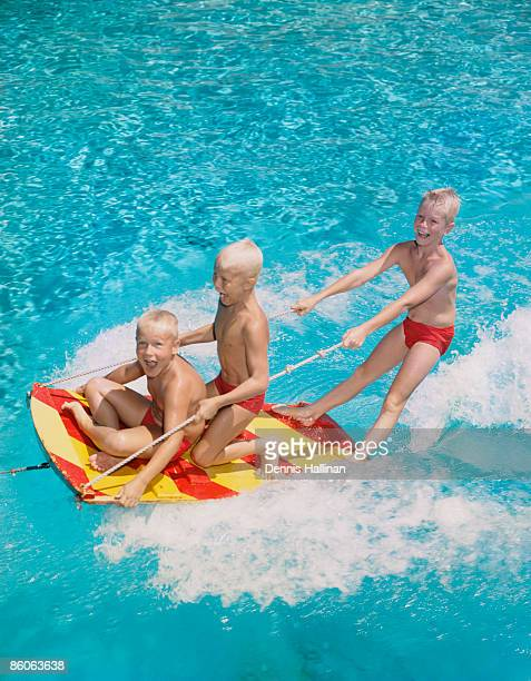 Three Boys Riding on a Water Sled