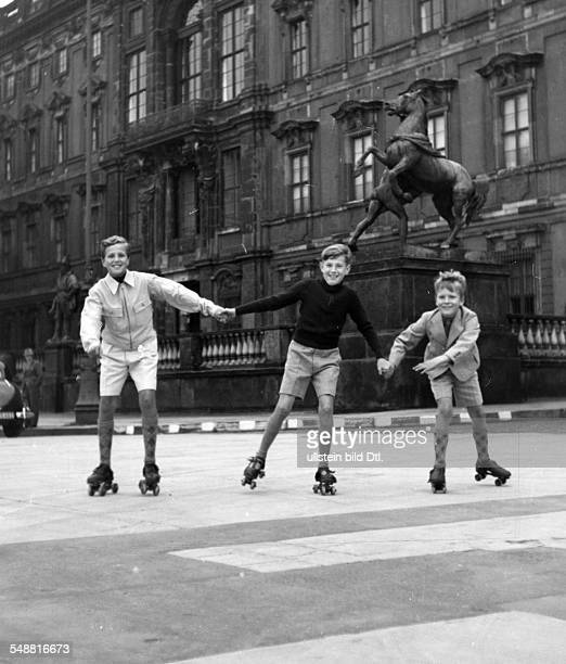 Three boys rollerskating in front of the 'Stadtschloss' in Berlin undated before 1942 Photographer Hedda Walther Vintage property of ullstein bild