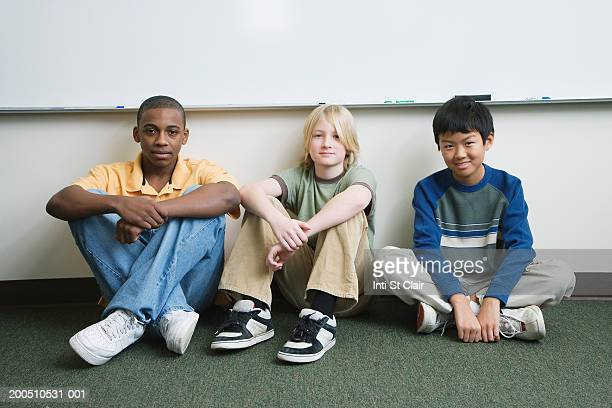 three boys (11-13) sitting on floor in front of whiteboard, portrait - only boys stock pictures, royalty-free photos & images