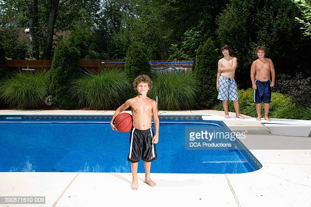 Three boys (8-14) standing at poolside, smiling, portrait