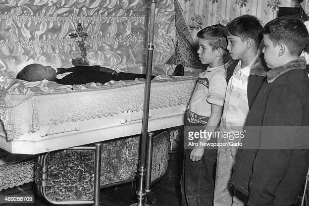 Three boys standing next to the open coffin of a boy 1960