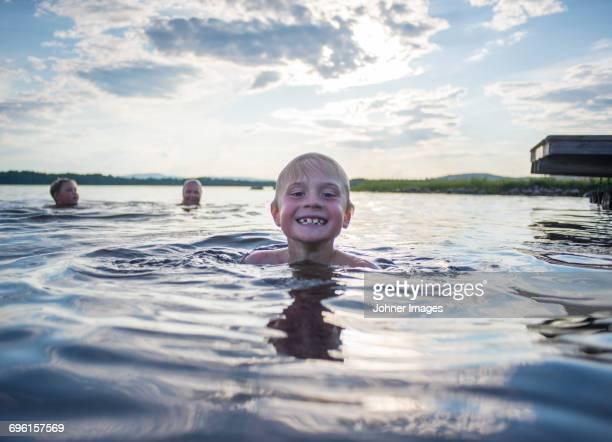 three boys swimming in lake - レクサンド ストックフォトと画像