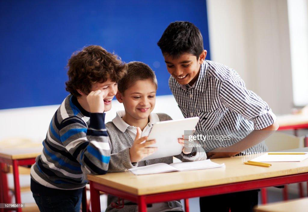 three boys using tablet computer in classroom : Foto de stock