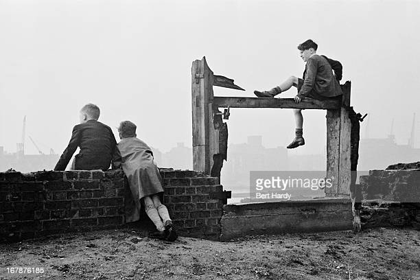 Three boys watching the shipping in the Pool of London from the north bank of the Thames at Wapping east London December 1949 Original Publication...