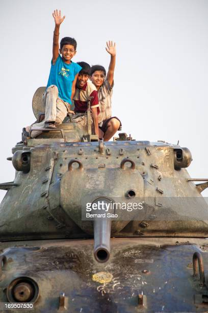Three boys wave hello from a Pakistani M47 Patton tank, a war trophy from a previous skirmish. Tank Bund Road, Hyderabad, India, 2008
