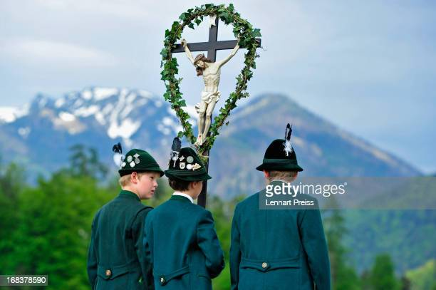 Three boys wearing Bavarian folk costumes specific to the Chiemsee region of southern Bavaria carry a cross during the annual Ascension Day...