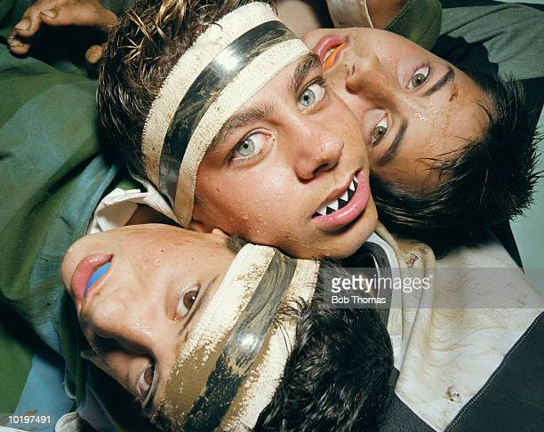 Three boys (12-14) wearing gum shields, portrait, close-up