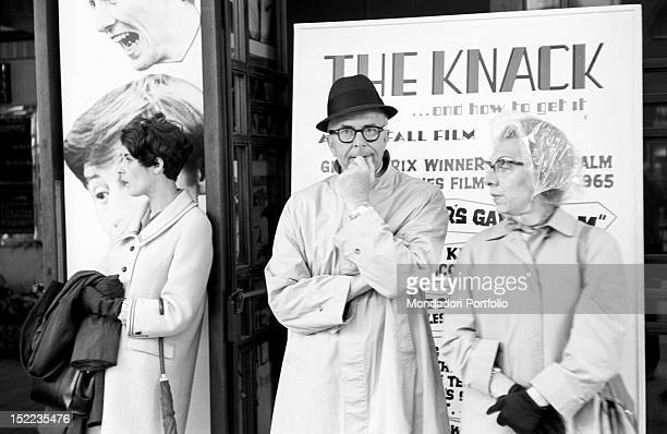 Three British citizens waiting in front of the poster of the film 'The Knack and How to Get It' The lady shelters from the rain with a plastic bonnet...