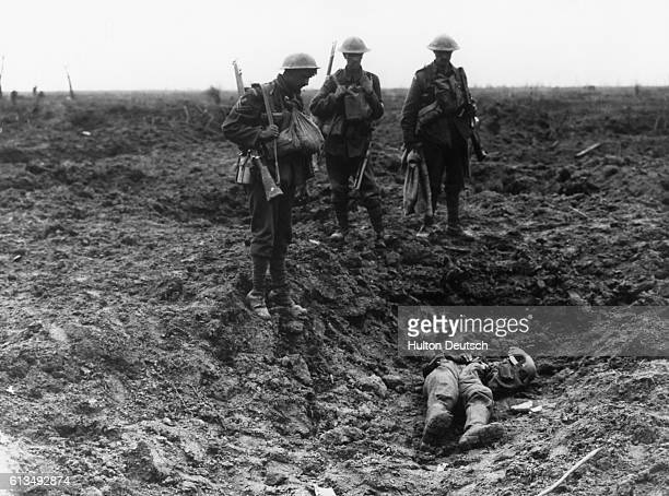 Three British guardsmen stand over the body of a dead German soldier lying in a shell crater near Ypres after the Battle of Pickle[u]n Ridge In the...