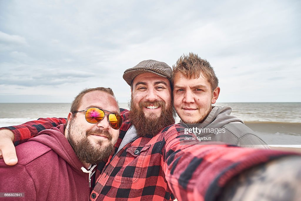 A group of three British male friends are fishing at the beach, they have stopped to take a selfie. Two of the males have beards and the third male has stubble.