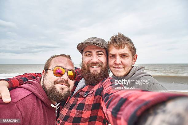 Three British males are posing for a selfie