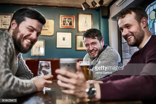 three british males sat together looking at a phone together laughing at it. - pub stock pictures, royalty-free photos & images