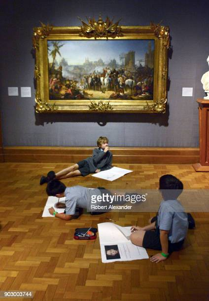 Three British students on a school field trip to the National Portrait Gallery in London England work on their drawing assignments