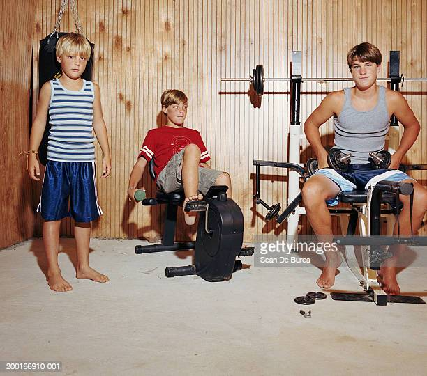 Three brothers (8-15) in home gym, portrait