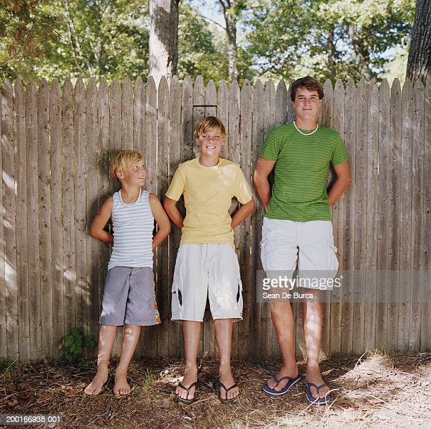 three brothers (8-15) leaning against fence in backyard, portrait - teen boy barefoot stock photos and pictures