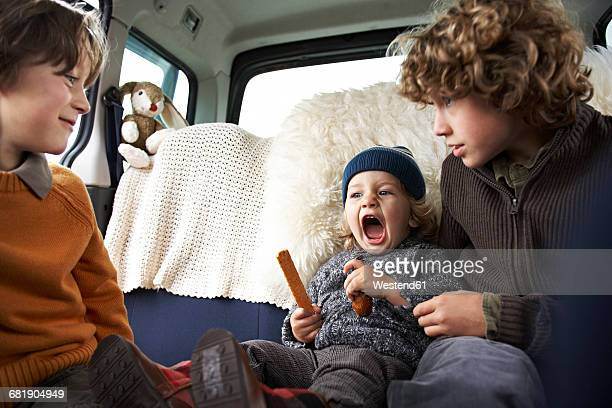 Three brothers playing in car