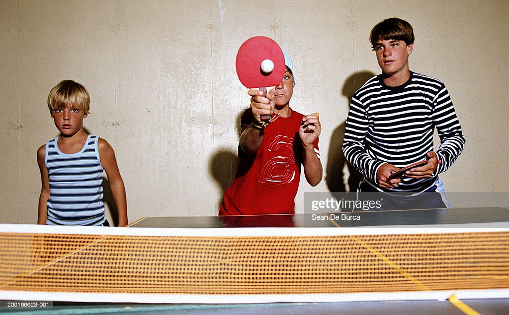Three brothers (8-15) playing table tennis : Stock Photo