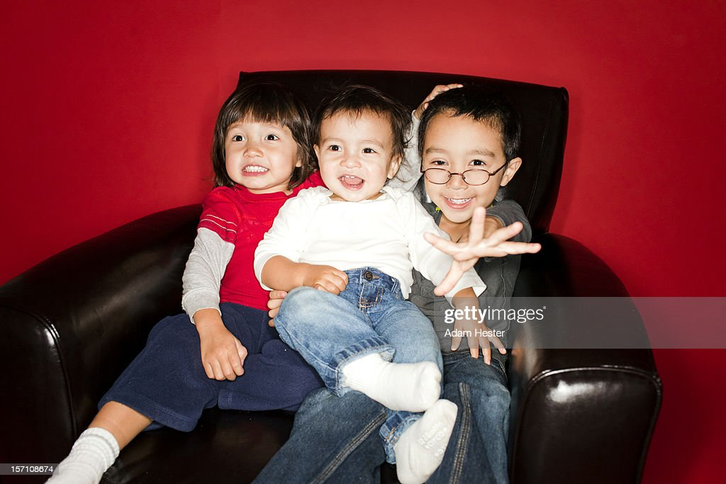Three brothers sitting in a chair together. : Stock Photo