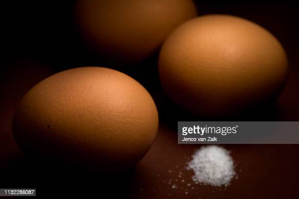 Three brown eggs and salt
