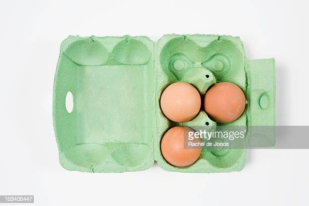 Three brown eggs in an egg carton
