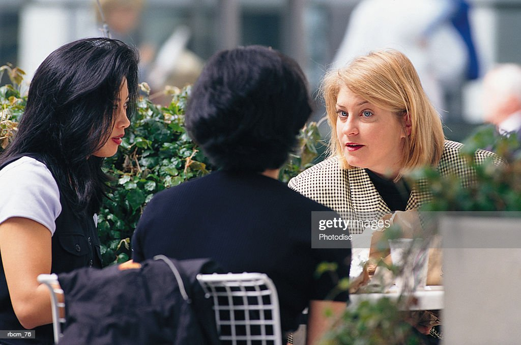 Three brunette businesswomen converse while sitting outside and eating lunch : Stockfoto