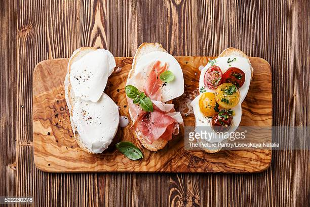 Three bruschettas with mozzarella cheese, ham and roasted tomato