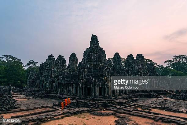Three buddhist monks walking in Angkor temple