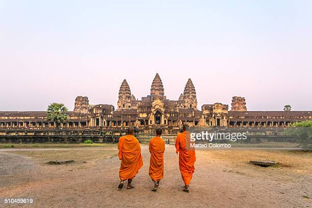 Three buddhist monks walking to Angkor Wat temple