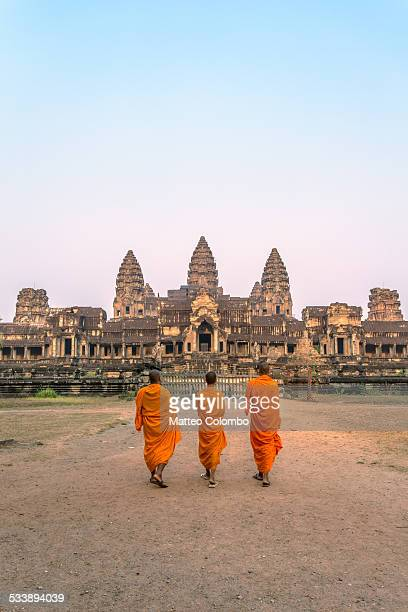three buddhist monks walking to angkor wat temples - kambodschanische kultur stock-fotos und bilder